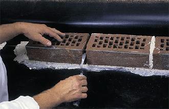 Удаление раствора из вертикального вентиляционного шва в нижнем ряде кирпичной кладки